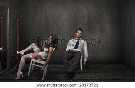 Attractive couple in a dark room - stock photo