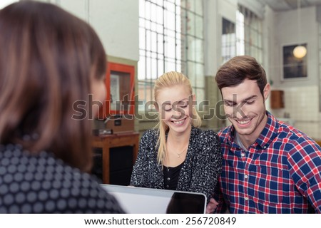 Attractive couple in a meeting with a broker or agent sitting across the desk from her smiling as they read through a presentation - stock photo
