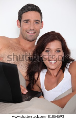 Attractive couple in bed with a laptop - stock photo