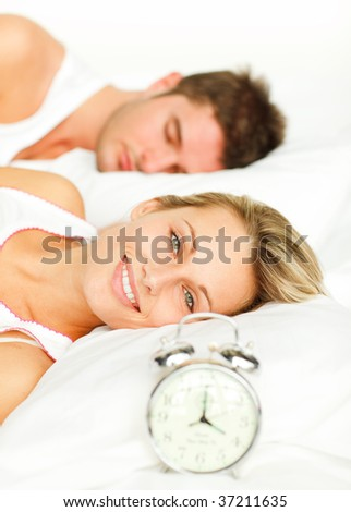 Attractive couple in bed with alarm clock and woman smiling at the camera