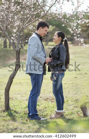 Attractive couple in blossoming park. Asian girl and european guy standing against of blossoming almond tree
