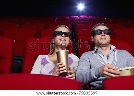 Attractive couple in 3D glasses watching movies in cinema