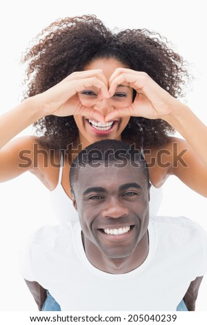Attractive couple in matching clothes smiling at camera on white background - stock photo