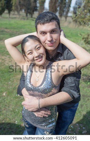 Attractive couple in park. Asian girl and european guy posing on open air looking at camera smiling - stock photo