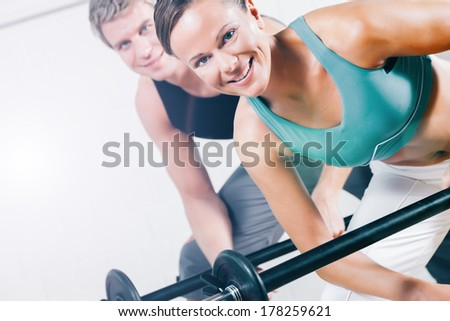 attractive couple in sport gym doing power gymnastics training with barbells - stock photo