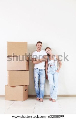Attractive couple in the apartment with a cardboard box - stock photo