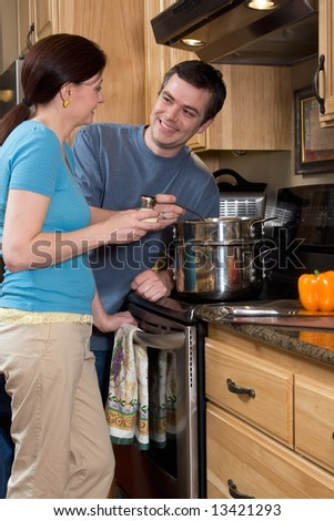 Attractive couple in the kitchen smiling at each other while standing by the stove. Vertically framed close-up shot. - stock photo