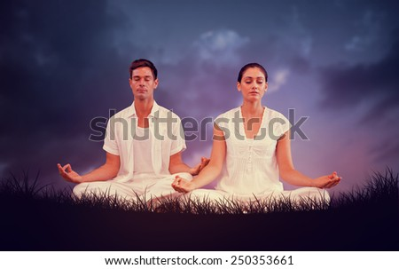 Attractive couple in white meditating in lotus pose against blue sky over grass - stock photo