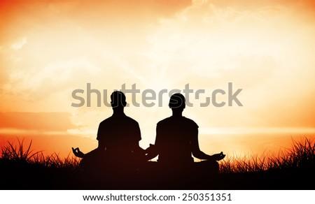 Attractive couple in white meditating in lotus pose against orange sunrise - stock photo