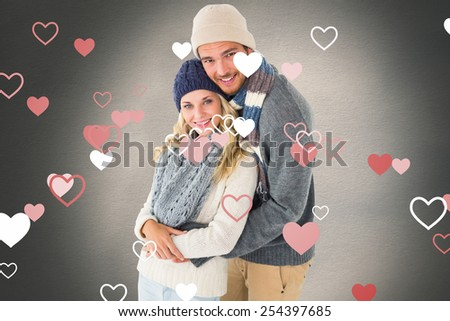Attractive couple in winter fashion hugging against white background with vignette - stock photo