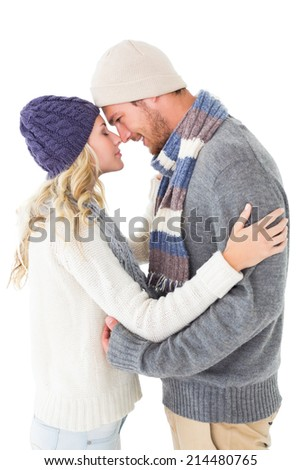 Attractive couple in winter fashion hugging on white background - stock photo