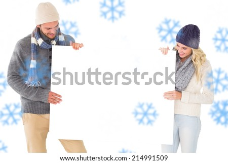 Attractive couple in winter fashion showing poster against snowflakes - stock photo
