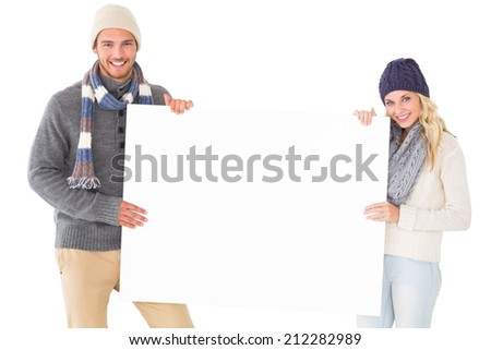 Attractive couple in winter fashion showing poster on white background - stock photo