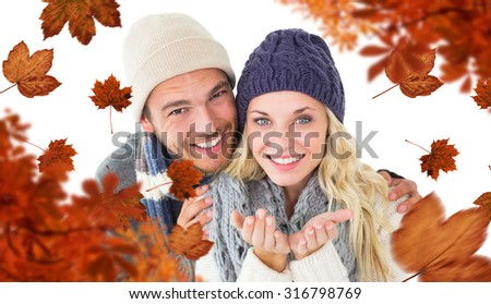 Attractive couple in winter fashion smiling at camera against autumn leaves - stock photo