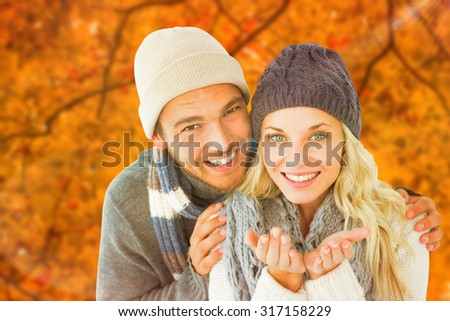 Attractive couple in winter fashion smiling at camera against autumn scene - stock photo