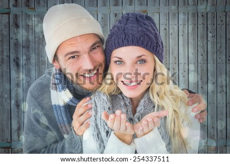 Attractive couple in winter fashion smiling at camera against blue abstract light spot design - stock photo