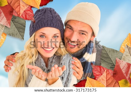 Attractive couple in winter fashion smiling at camera against blue sky - stock photo