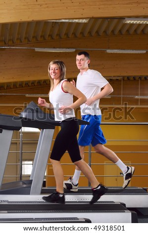 attractive couple is running on the treadmill - stock photo