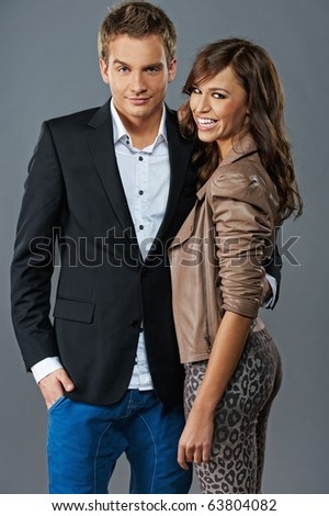 Attractive couple isolated on grey background - stock photo