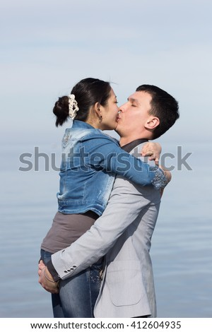 Attractive couple kissing against of sea. Asian girl and european guy kissing on background of sea - stock photo