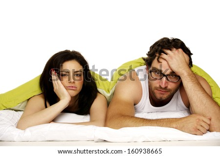 Attractive couple laid in bed under a green duvet looking tired and miserable in the morning