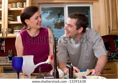 Attractive couple laughing and sharing a joke while doing the dishes in the kitchen. Horizontally framed shot. - stock photo