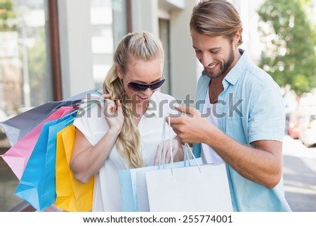 Attractive couple looking at shopping purchases on a sunny day in the city - stock photo