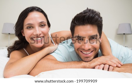 Attractive couple lying on bed smiling at camera at home in bedroom
