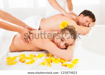 Attractive couple lying side by side in a spa enjoying the luxury of a deep tissue back massage together - stock photo