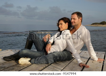attractive couple on a pier - stock photo