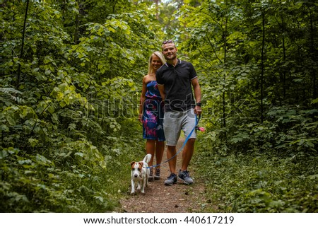Attractive couple on a walk with a dog in a wood. - stock photo