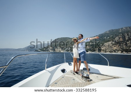 Attractive couple on a yacht enjoy bright sunny day on vacation