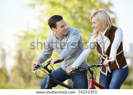 Attractive couple on bicycles looking at each other - stock photo