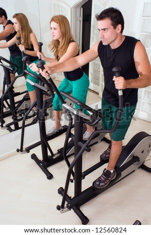 Attractive couple on elliptical trainers at the gym. Vertically framed shot. - stock photo