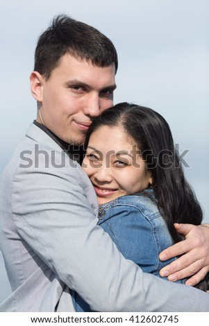 Attractive couple on open air. European guy embracing Korean girl - stock photo