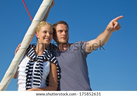 Attractive couple on sailing boat: man pointing with forefinger at something. - stock photo