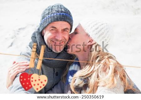 Attractive couple on the beach in warm clothing against hearts hanging on the line - stock photo