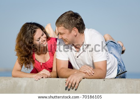 Attractive couple outdoors. Young man and young woman lying on front and smiling