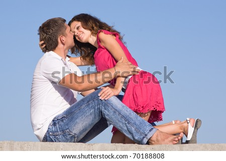 Attractive couple outdoors. Young man and young woman on background of sky