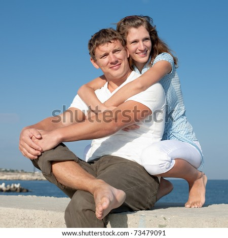 Attractive couple outdoors. Young man and young woman on background of sky - stock photo