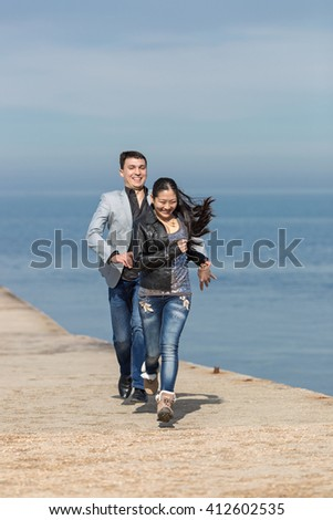 Attractive couple playing catch-up on concrete pier. European guy catches his asian girlfriend - stock photo