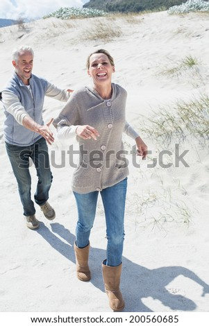 Attractive couple playing chasing on the beach on a bright but cool day - stock photo