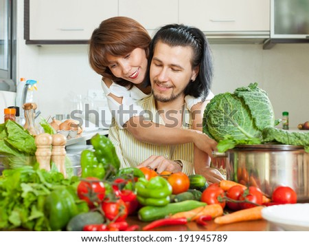 Attractive couple preparing vegetable salad in my house