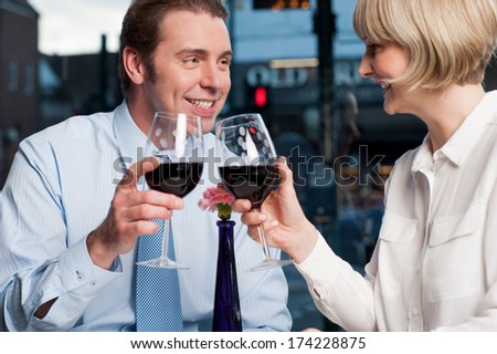 Attractive couple raises a glass of red wine in cafe - stock photo