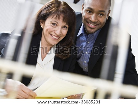 Attractive couple reading paper. Male above female, in business suits. Horizontal. - stock photo