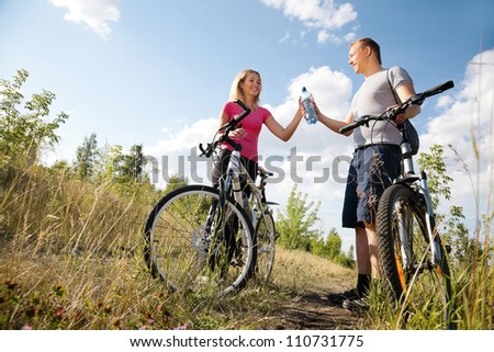 Attractive couple refreshing after biking in the forest - stock photo