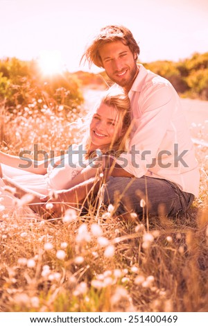 Attractive couple relaxing in the countryside on a sunny day - stock photo