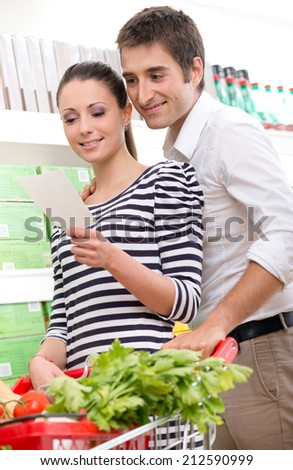 Attractive couple shopping at supermarket with shopping list. - stock photo