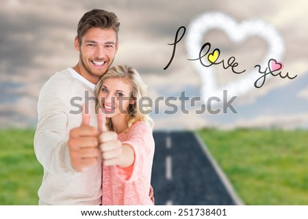 Attractive couple showing thumbs up to camera against road on grass - stock photo