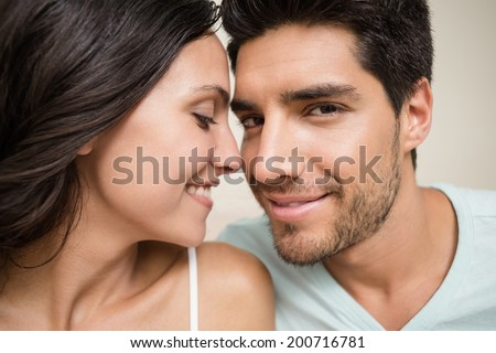 Attractive couple sitting on bed at home in bedroom